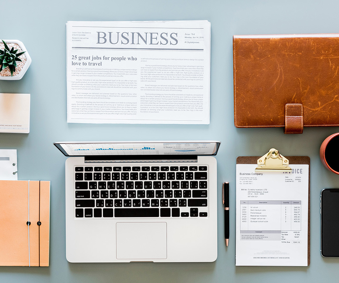 A photo of a desk with a newspaper, coffee, cell phone, and notepad