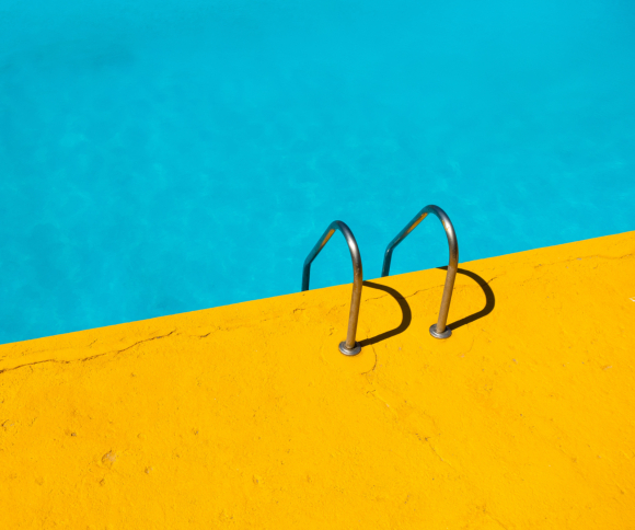 A photo of a swimming pool and ladder with blue and yellow cement