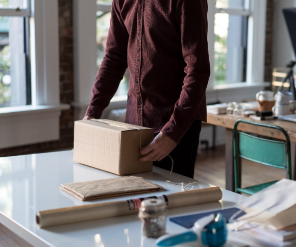 A photo of a person packing a box with products