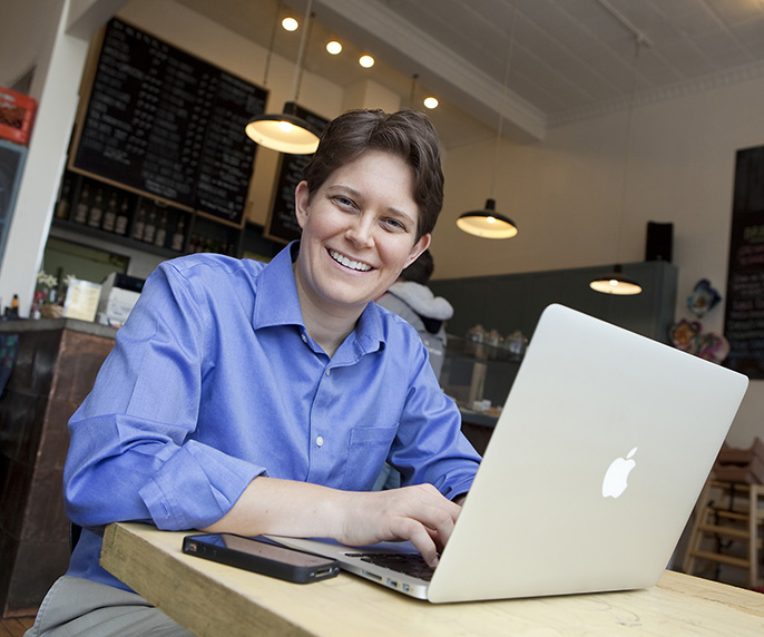 A photo of Dorie Clark with a Mac computer