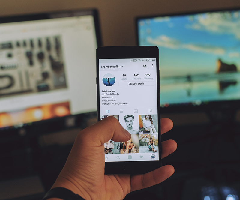 A photo of a person holding up a phone showing the Instagram feed