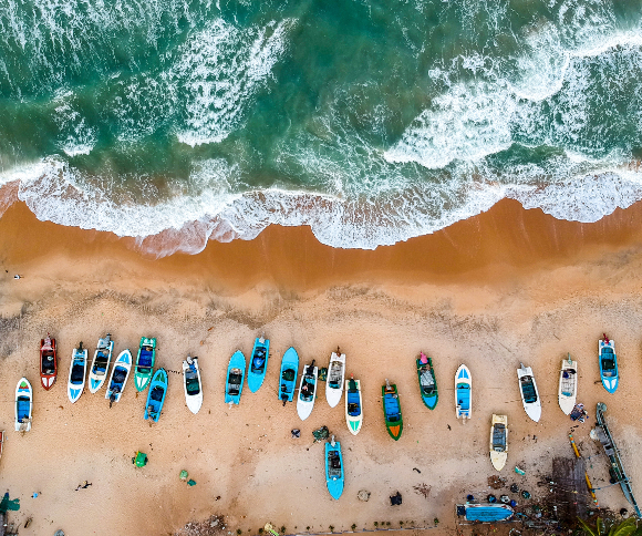 A photo of a beach from above with ocean and boats