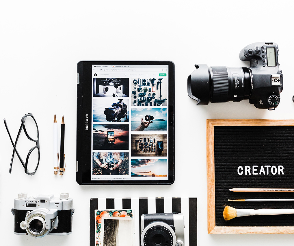A photo of a camera and iPad on a white desk