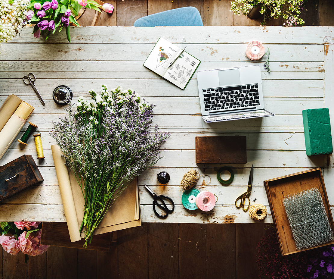 A photo of a desk with flowers, a Mac, and a blank notepad for writing marketing ideas